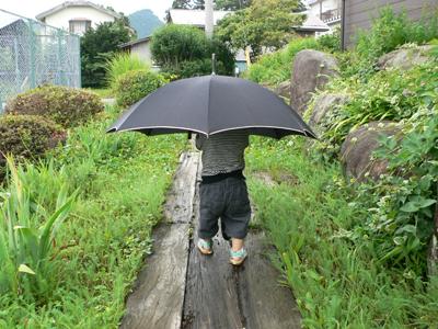 傘をさす息子